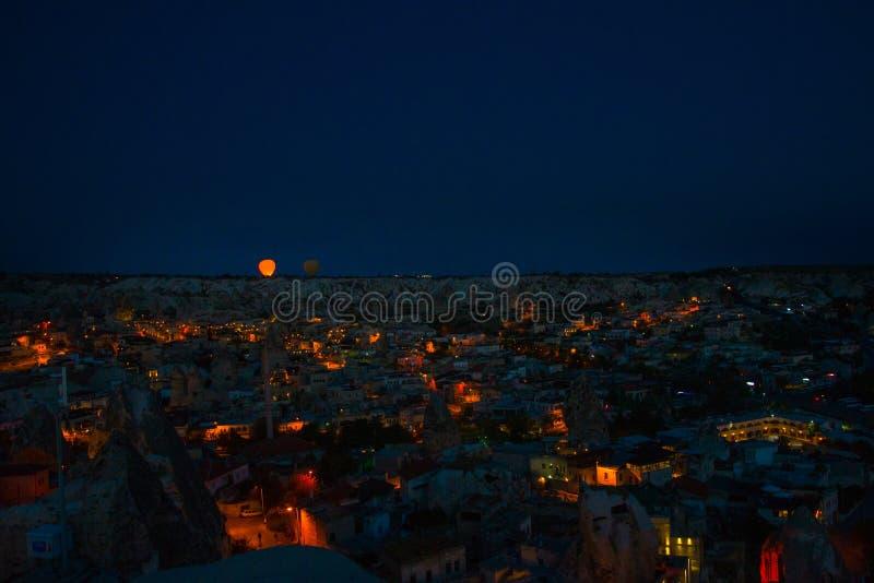 Illuminated at night streets of Goreme, Turkey, Cappadocia. The famous center of flight balloons. On the horizon - highlighted royalty free stock image