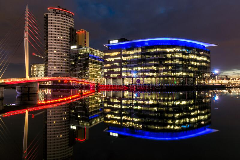 Illuminated office buildings reflected in quayside water with modern bridge at Salford Quays, UK. stock image