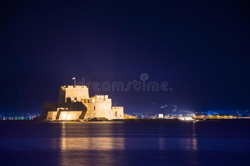 Illuminated old town of Nafplion in Greece with tiled roofs, small port, bourtzi castle, Palamidi fortress. Illuminated old town of Nafplion in Greece with stock photo