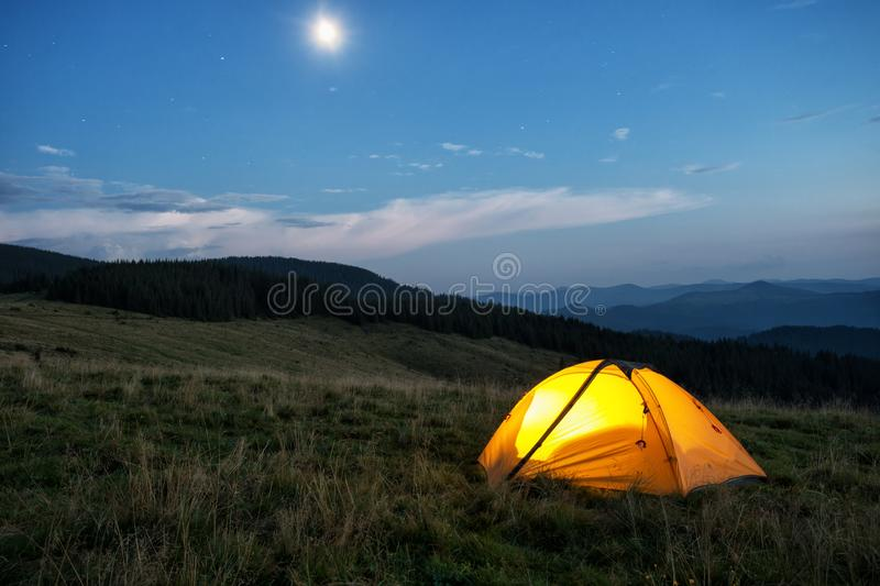 Illuminated orange tent in mountains at dusk stock images