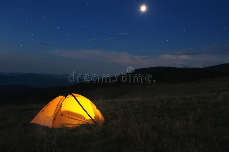 Illuminated orange tent at top of mountain at night stock photography