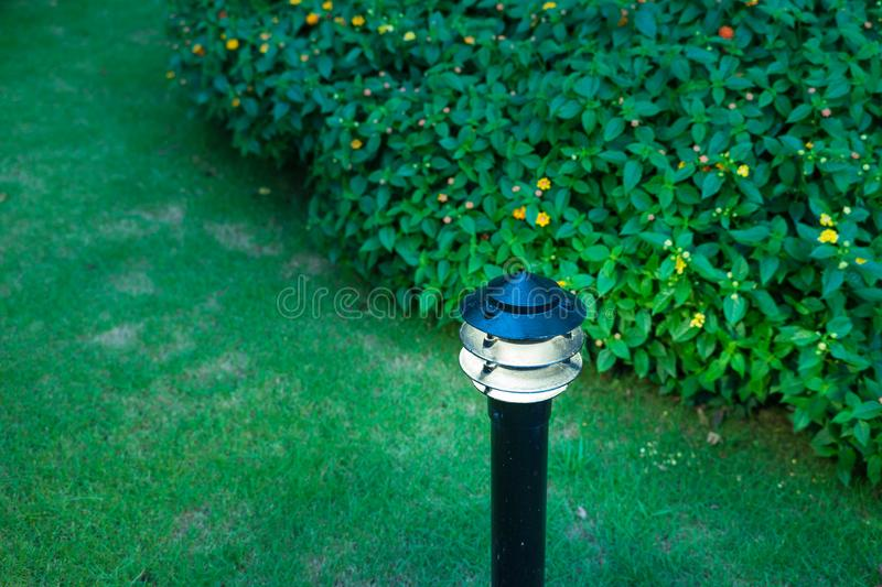 Illuminated outdoor light in apartment garden at twilight, evening.  royalty free stock image