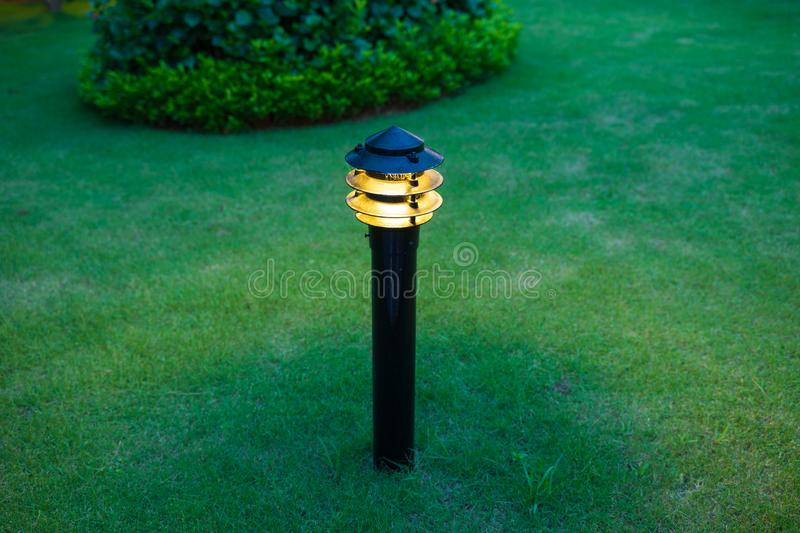 Illuminated outdoor light in apartment garden at twilight, evening.  royalty free stock images