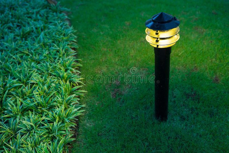 Illuminated outdoor light in apartment garden at twilight, evening.  royalty free stock photography