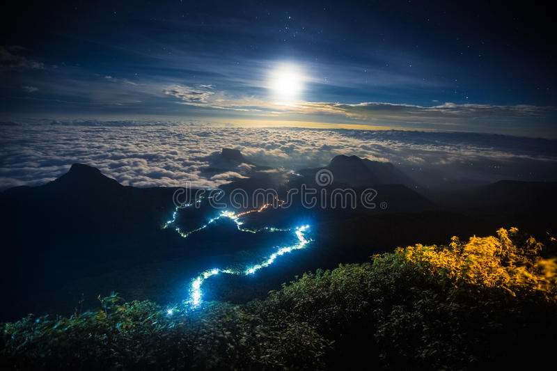 Illuminated path to the top of the mountain of Adams Peak. With moon and stars in the sky. View from Adams Peak, Sri Lanka stock photos