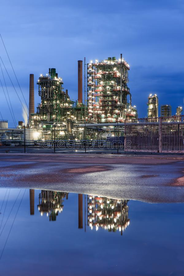 Illuminated petrochemical production plant at twilight with dramatic clouds reflected in a pond, Antwerp, Belgium. Illuminated petrochemical production plant at stock photography