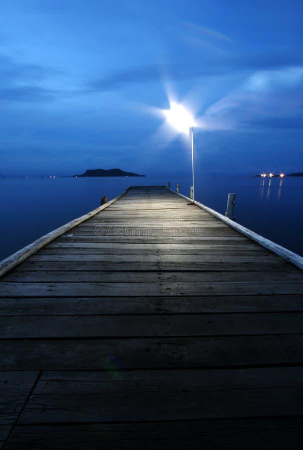 Illuminated Pier. A single light illuminating a pier by the sea royalty free stock photography