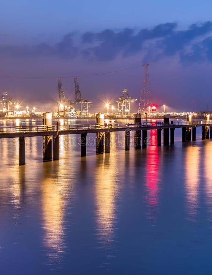 Illuminated pier in river Scheldt with container terminal, Port of Antwerp, Belgium. Illuminated pier in river Scheldt with container terminal on the background royalty free stock image