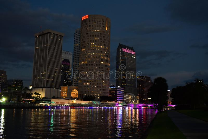 Illuminated Purple Bridge Over River In City Against Sky. stock photos