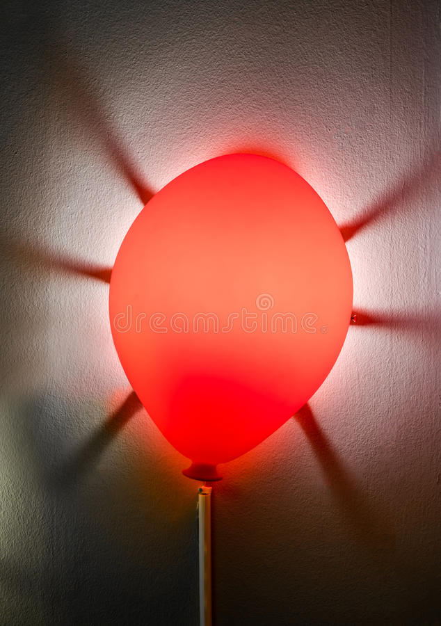 Illuminated red lamp attached on grey wall with scattered dark s stock photo