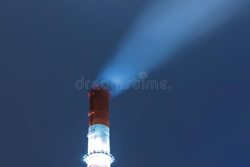 The illuminated red and white tube or pipe of the thermal power plant on the background of blue night or evening sky royalty free stock image