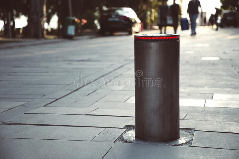 Illuminated retractable automatic traffic bollard protects pedestrian zone. Safety concept. Blurred people on background stock photography