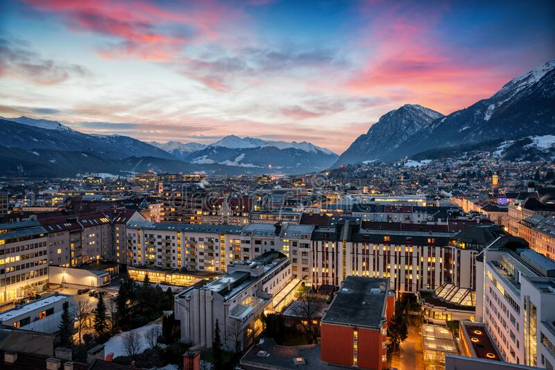 The illuminated skyline of Innsbruck in the Austrian Alps with snow. Elevated panorama of the illuminated skyline of Innsbruck in the Austrian Alps during winter royalty free stock photos