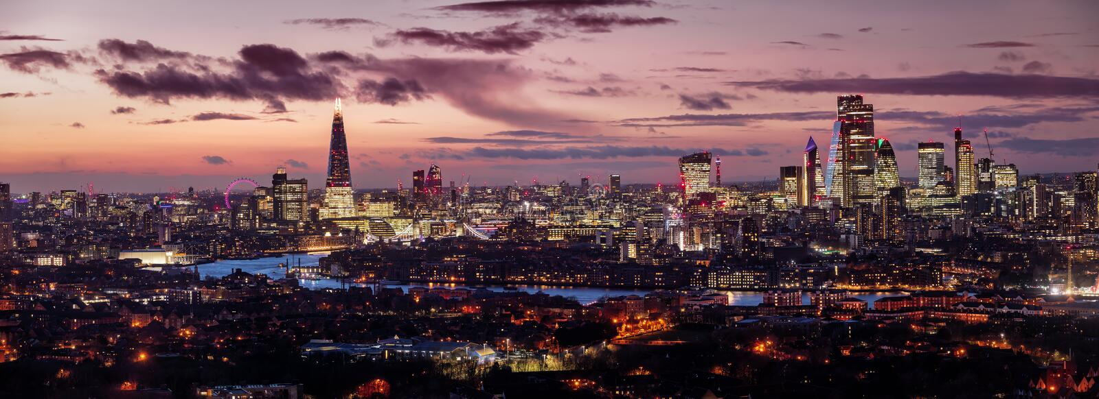 The illuminated skyline of London, United Kingdom, after a sunset. Wide panoramic view of the illuminated skyline of London, United Kingdom, after a sunset with royalty free stock images
