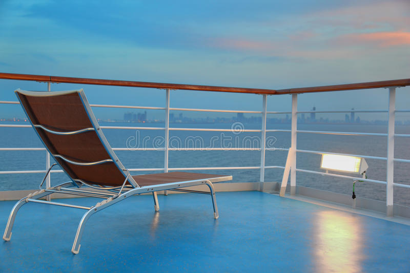 Illuminated solitary deck-chair on ship