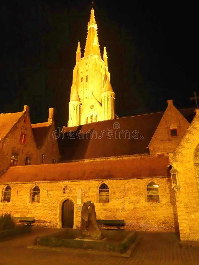 Illuminated spire of historic cathedral. The illuminated spire of the Church of Our Lady cathedral in the city of Bruges in Belgium royalty free stock photo