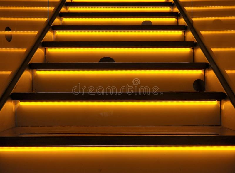 An yellow or orange colored illuminated stairway. Illuminated or neon colored stairway, striking background with yellow and orange colors . Funny mouseholes and stock photography