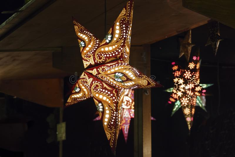 Illuminated stars in coloured colours on the Christmas market stock image