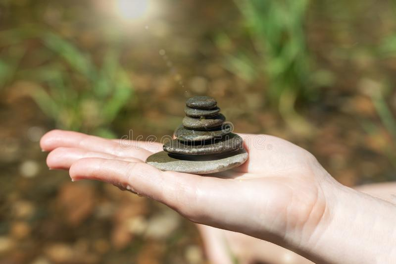 Sunlit pebble pyramid in the palm of the hand against the ocean stock photography