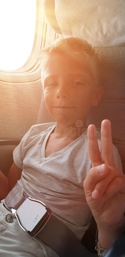 illuminated by sun from window, boy sits at window in plane and shows sign of victory royalty free stock photos