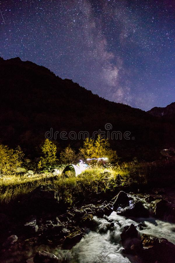 Illuminated tent on Baduk river and valley at night stock photography