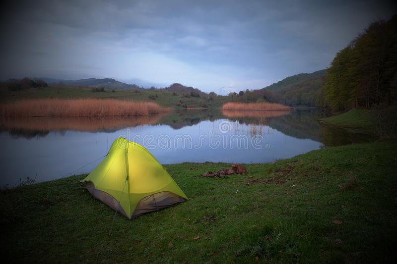 Illuminated tent by the Biviere Lake in Nebrodi Park. In overcast evening, Sicily stock photography