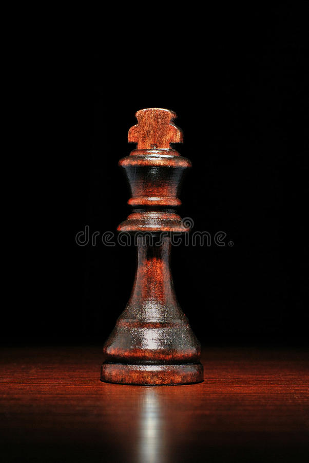 Illuminated wooden king chess piece. Close up view of a single illuminated wooden king chess piece on a reflective wooden surface against a dark background stock photos
