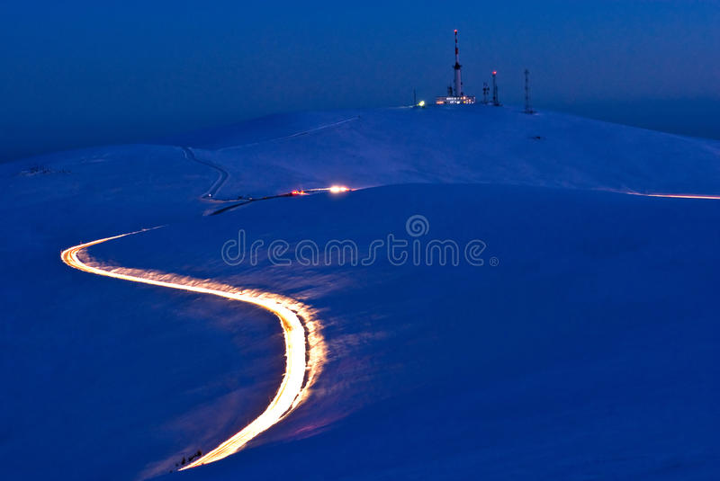 Illuminati. Trail of car headlights in motion on a high mountain raoad at night royalty free stock image