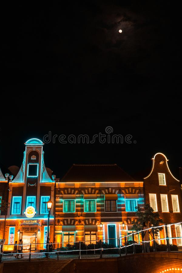 Illumination building and moon in the sky royalty free stock photo
