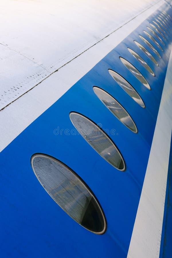Illuminators on fuselage. Windows of the white airplane fuselage with blue line stock photo