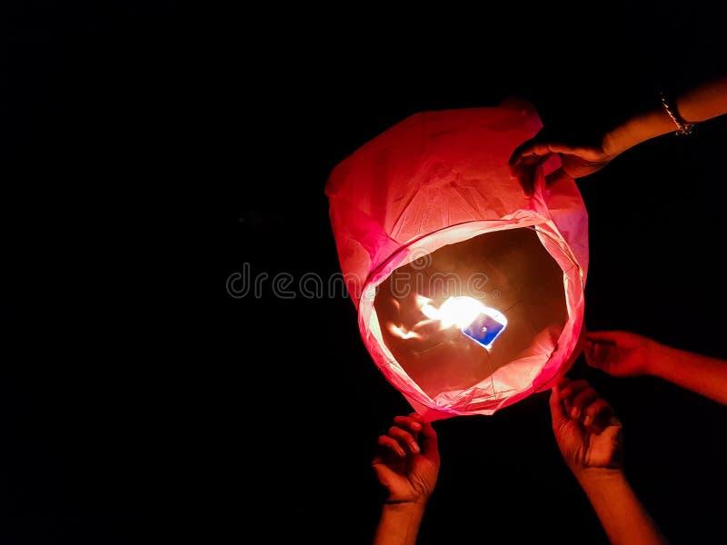Illuminazione della lanterna del cielo da un paio delle mani che tengono la mongolfiera di carta in un fondo nero fotografia stock libera da diritti