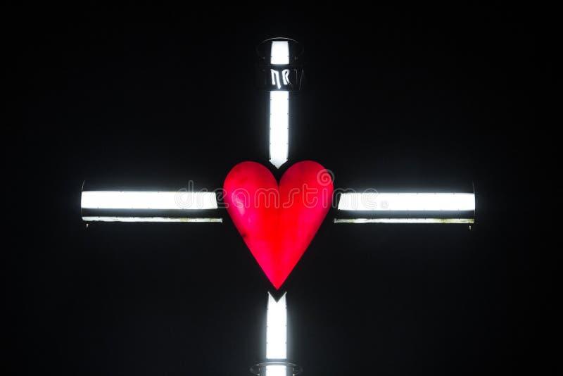 Illuminazione di un incrocio con cuore rosso immagine stock