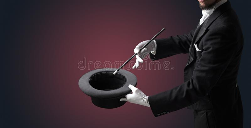 Illusionist hand want s to conjure something. Illusionist white hand wants to conjure with magic wand from a black cylinder something stock photos