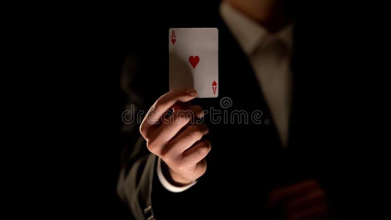 Illusionistvisningöverdängare av hjärtakortet på kameran, magiskt trick, svart bakgrund royaltyfria foton