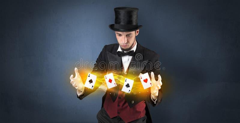 Illusionniste faisant le tour avec les cartes magiques de jeu photos stock