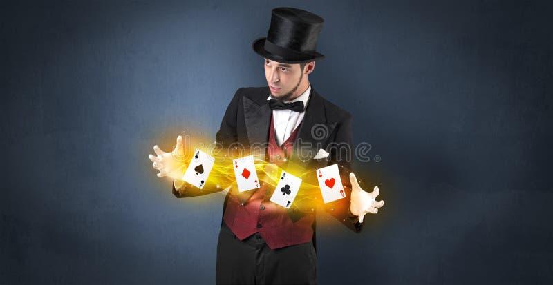 Illusionniste faisant le tour avec les cartes magiques de jeu photographie stock