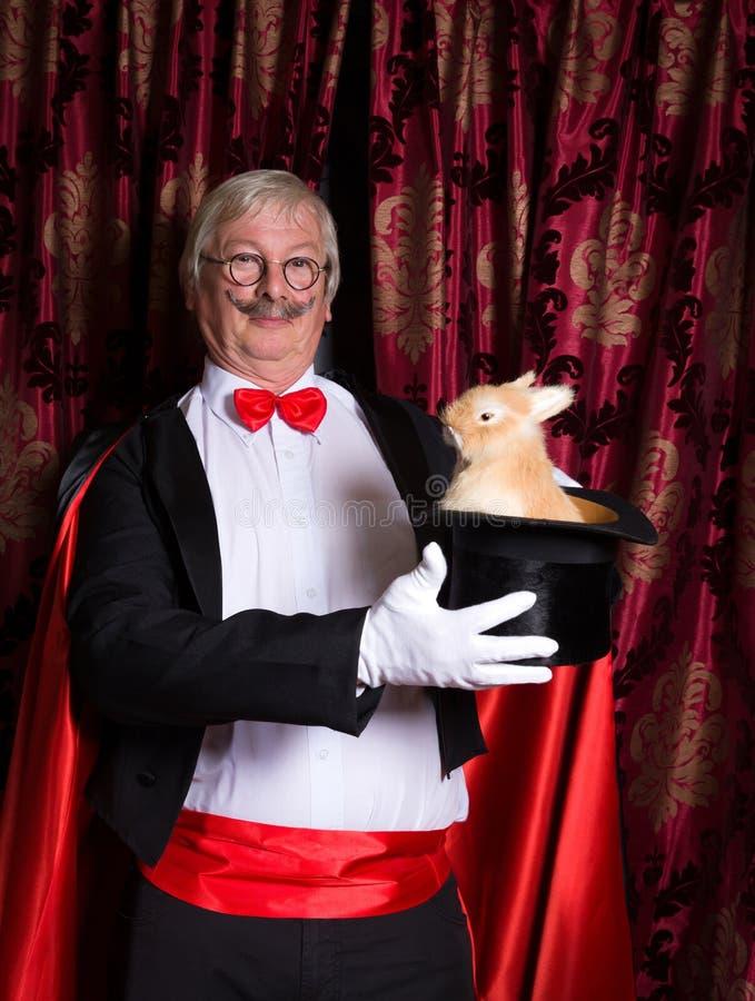 Illusionniste heureux avec le lapin images stock