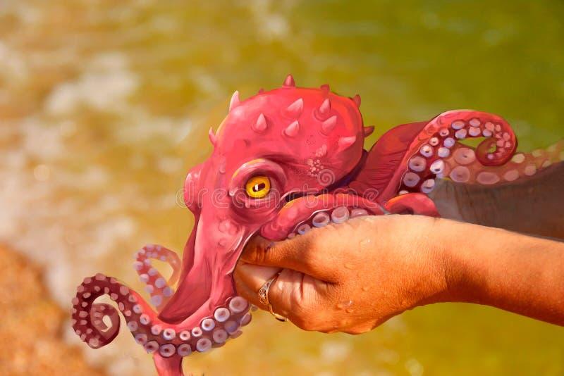 Illustratie van een rode octopus op de handen royalty-vrije illustratie