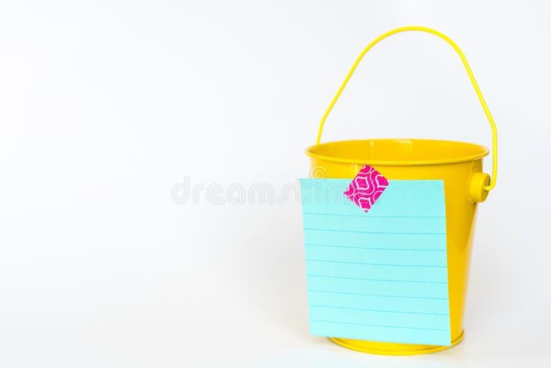 Illustratie van het concept van de emmerlijst met gele die metaalemmer en lijst aan voorzijde tegen witte achtergrond wordt vastg stock fotografie
