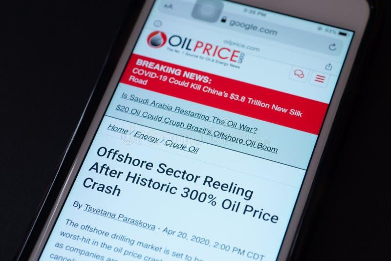 ILLUSTRATIEF EDITORIAAL - CIRCA APRIL 2020 : Screenshot van een Apple iPhone over nieuws over de crash van de ruwe olieprijs Nieu stock foto's