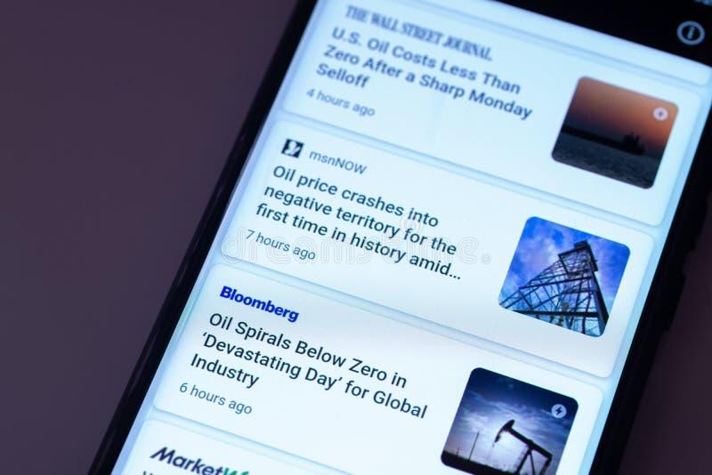 ILLUSTRATIEF EDITORIAAL - CIRCA APRIL 2020 : Screenshot van een Apple iPhone over nieuws over de crash van de ruwe olieprijs Nieu stock foto