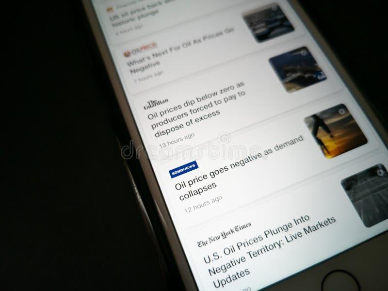 ILLUSTRATIEF EDITORIAAL - CIRCA APRIL 2020 : Screenshot van een Apple iPhone over nieuws over de crash van de ruwe olieprijs Nieu stock fotografie