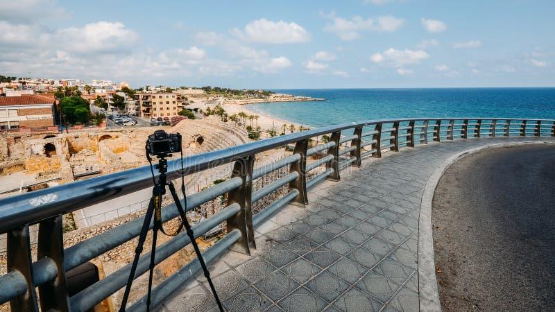 Illustratief hoofdartikel van Nikon D800 DSLR en driepoot met panorama van het oude roman amfitheater van Tarragona royalty-vrije stock foto