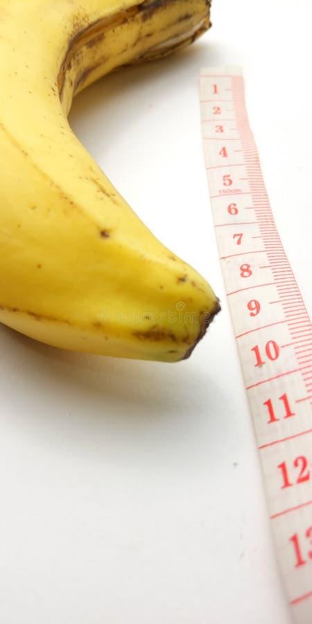 Illustration conceptuelle de photo simple pour la taille de pénis, banane avec le mètre en plastique rose de tailleur sur le fond photographie stock