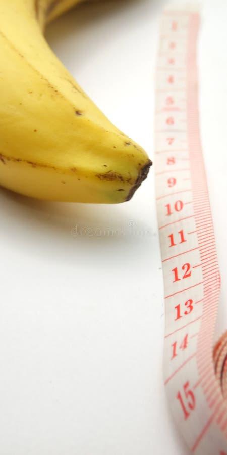 Illustration conceptuelle de photo simple pour la taille de pénis, banane avec le mètre en plastique rose de tailleur sur le fond photo stock