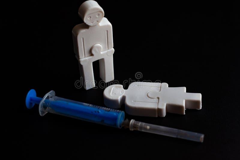 Illustration des effets de la dépendance petits hommes de plastique avec une seringue Concept photos stock