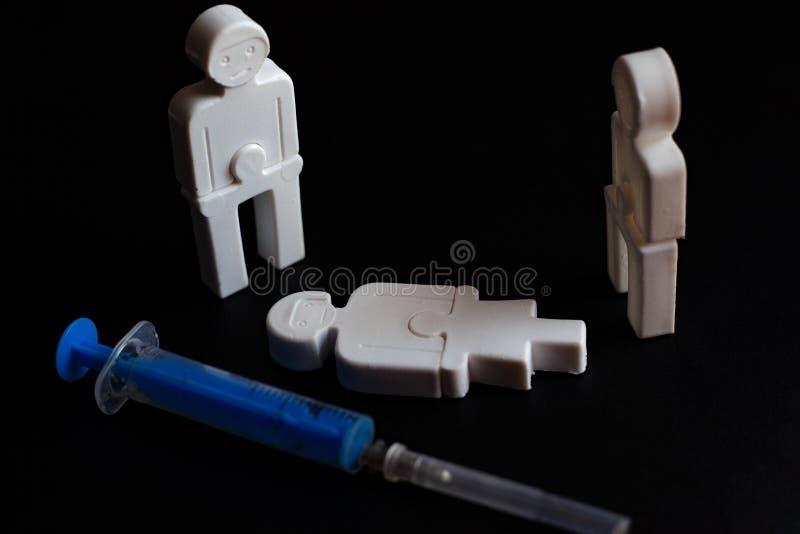 Illustration des effets de la dépendance petits hommes de plastique avec une seringue Concept photographie stock libre de droits