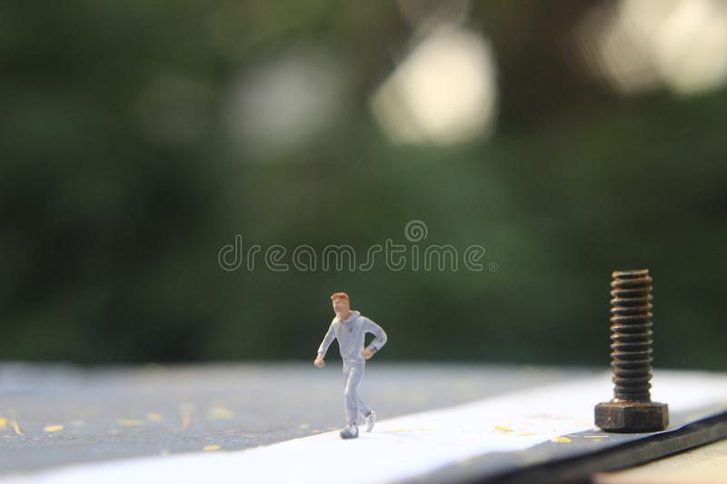 Illustration Foto, Cheap och Easy Sport på morgonen, Alone Mini Figur Sport Man Toy vid Asphalt Road royaltyfria bilder