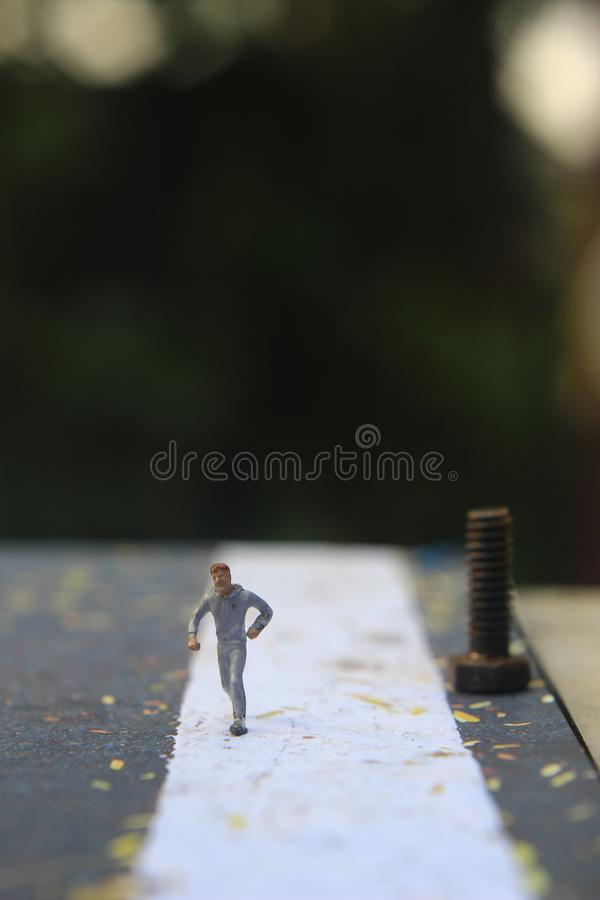 Illustration Foto, Cheap och Easy Sport på morgonen, Alone Mini Figur Sport Man Toy vid Asphalt Road arkivfoto