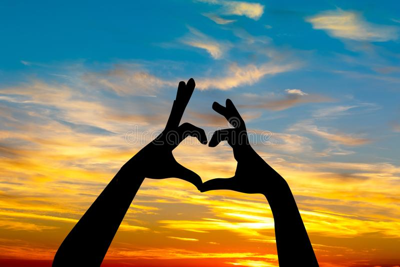 Hands forming a heart at sunset stock illustration